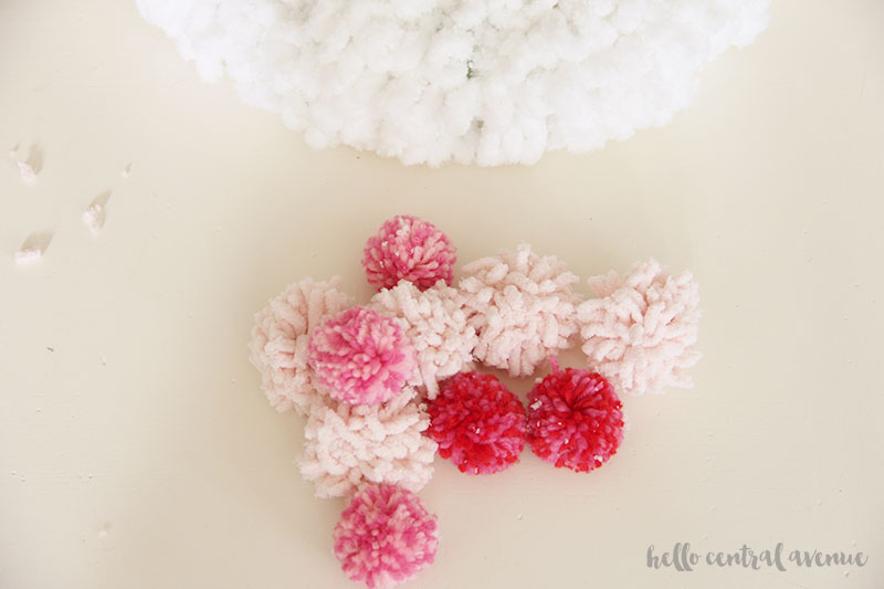 How to make an easy yarn and pom pom wreath for Valentine's Day to hang on your door. Make your yarn pom poms.