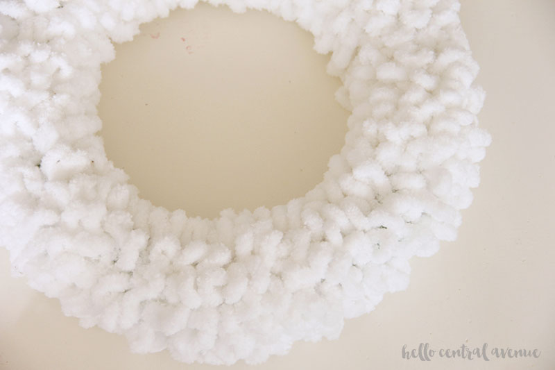How to make an easy yarn and pom pom wreath for Valentine's Day to hang on your door. Wrap the base in loopy yarn.