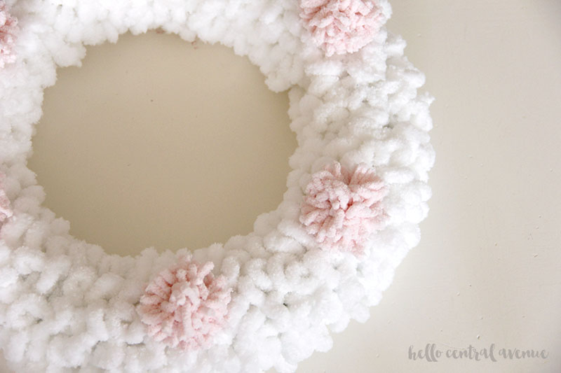 How to make an easy yarn and pom pom wreath for Valentine's Day to hang on your door. Glue on your pom poms.